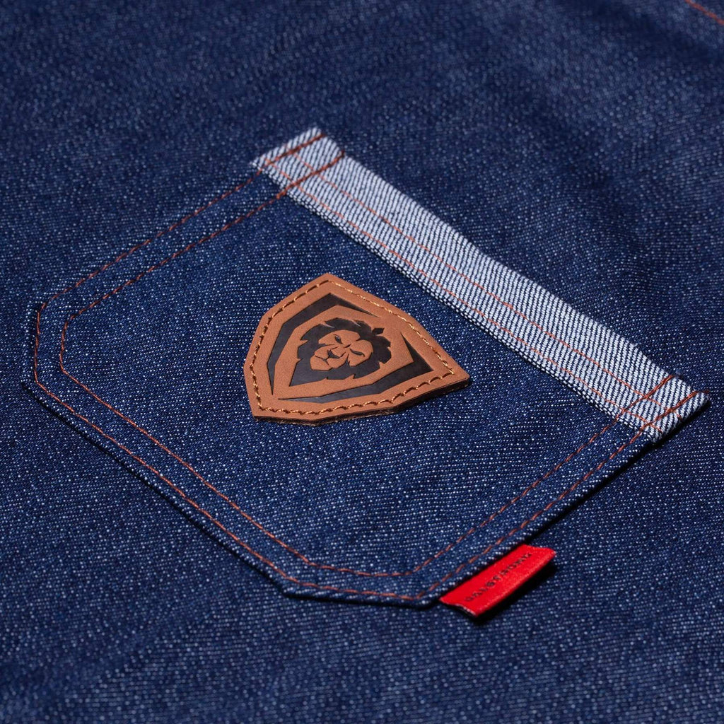 Close up on a blue apron's pocket with a brown Dalstrong lion logo