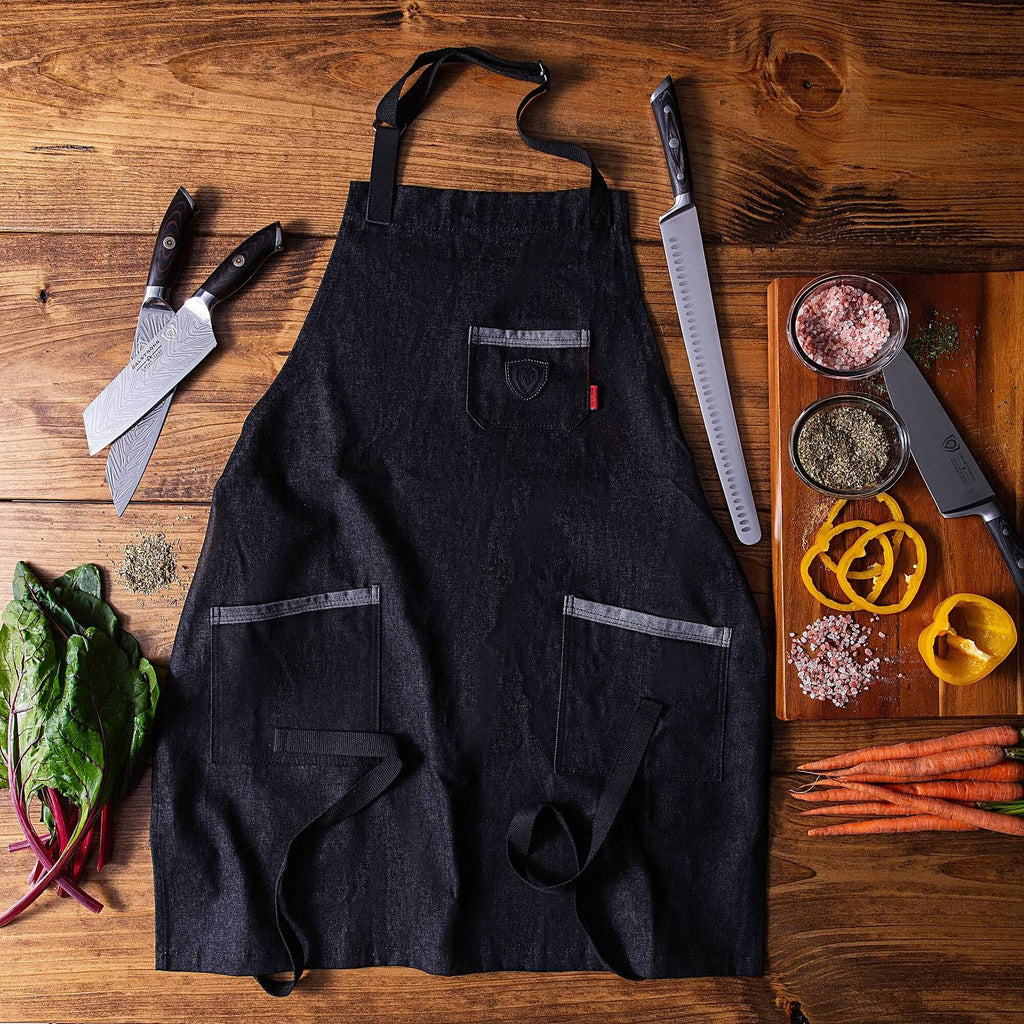 Black apron on a wooden floor next to chopped vegetables and sharp kitchen knives