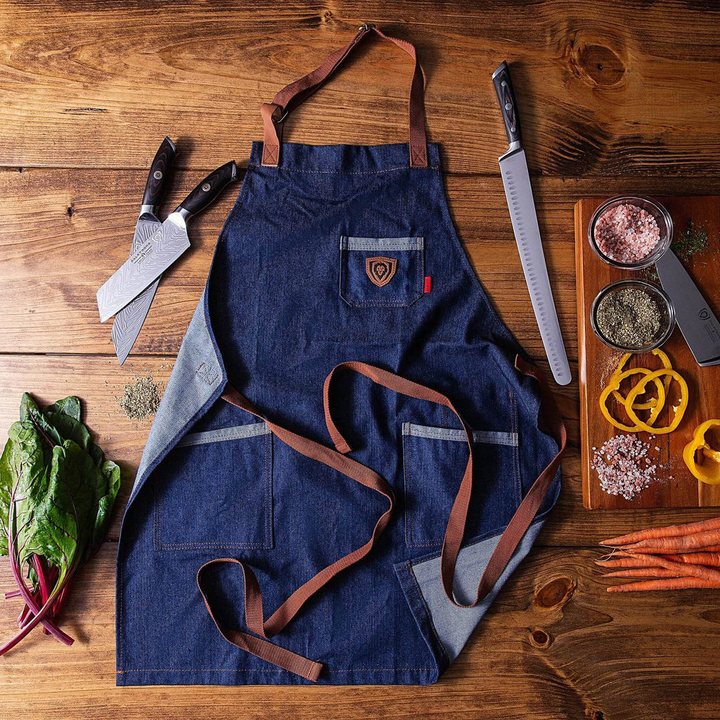 Navy blue kitchen apron with brown straps next to kitchen knives and sliced vegetables