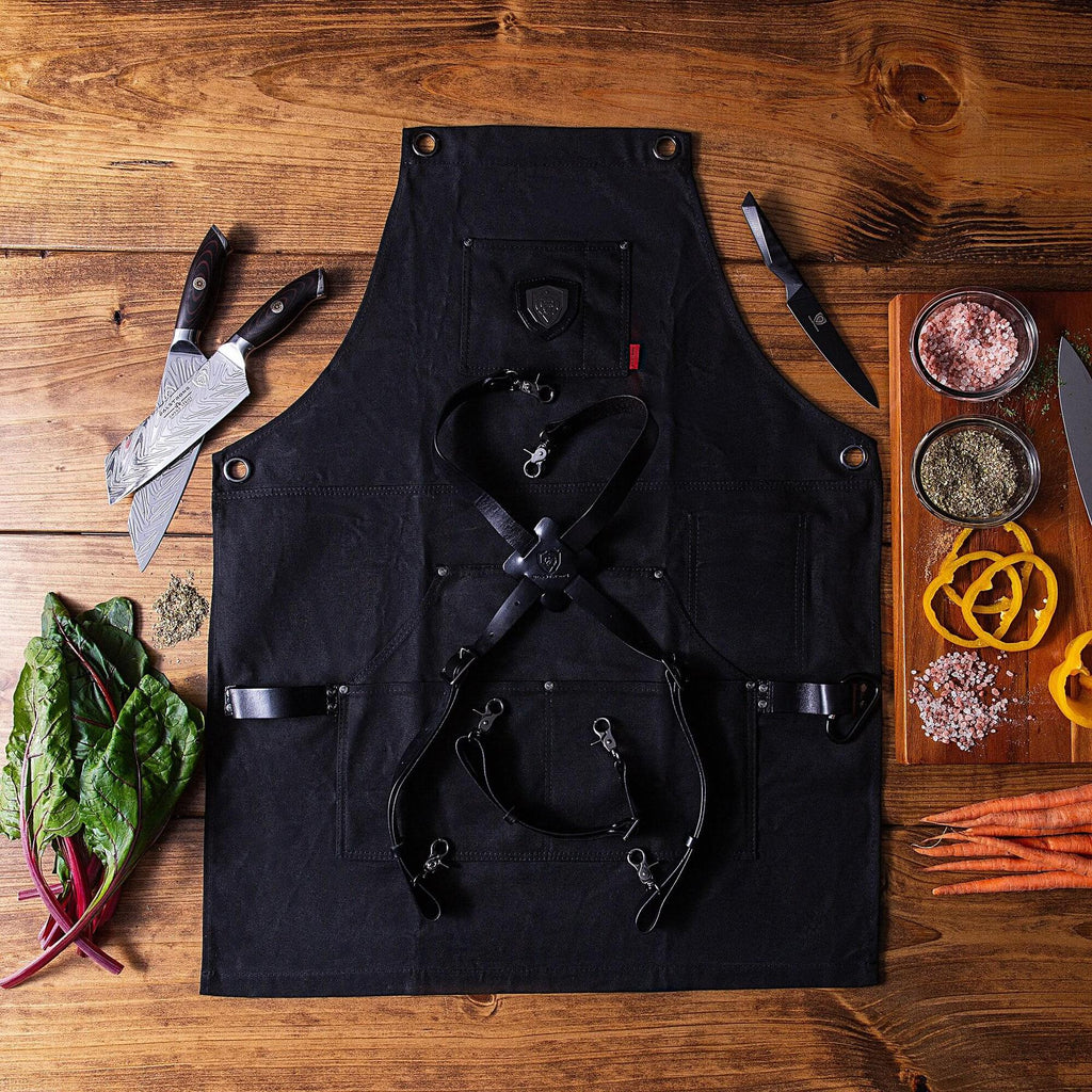 Black kitchen apron on a wooden floor next to chopped food and a kitchen knife
