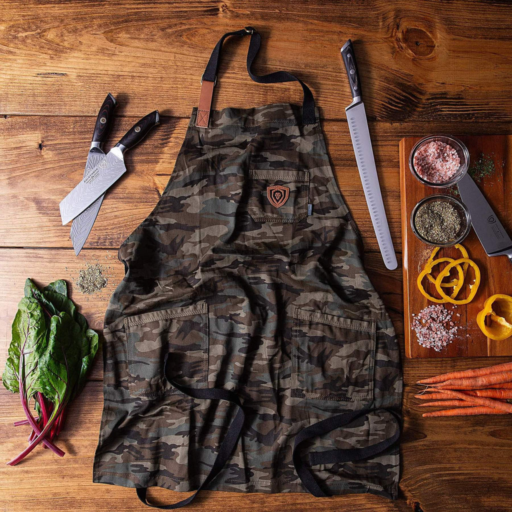 Green camouflage kitchen apron on a brown background next to chef knives and chopped peppers