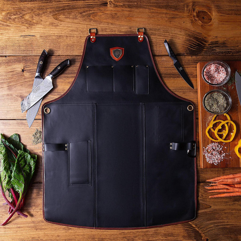 Black leather kitchen apron on a wooden floor next kitchen knives and chopped vegetables