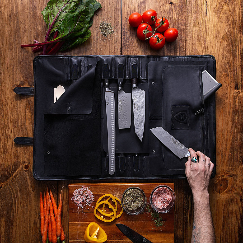 Black leather knife roll on a wooden table with several kitchen knives in it