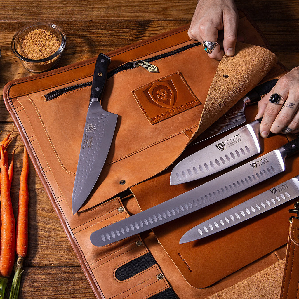 Four chef knives being placed into a brown leather knife roll with carrots next to it on a wooden table