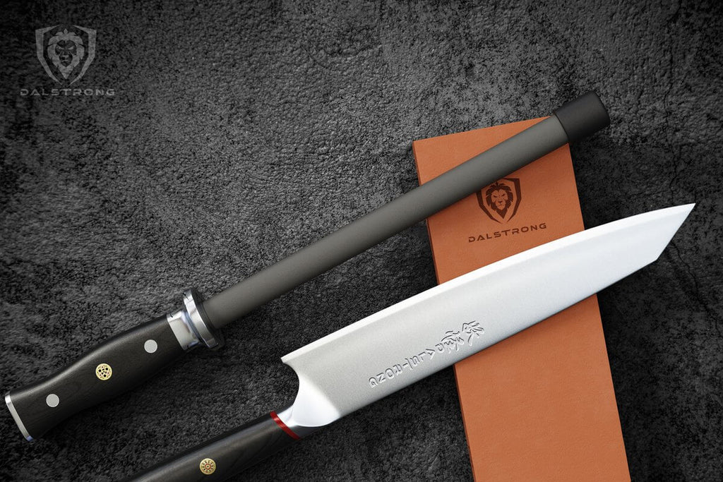 A black ceramic honing steel rests on an orange whetstone next to a chef knife against a black background