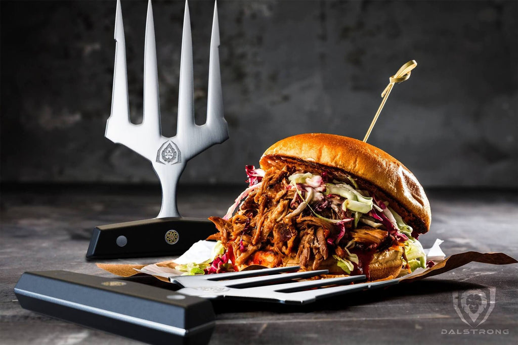A pulled pork sandwich on a plate with a meat claw in the background