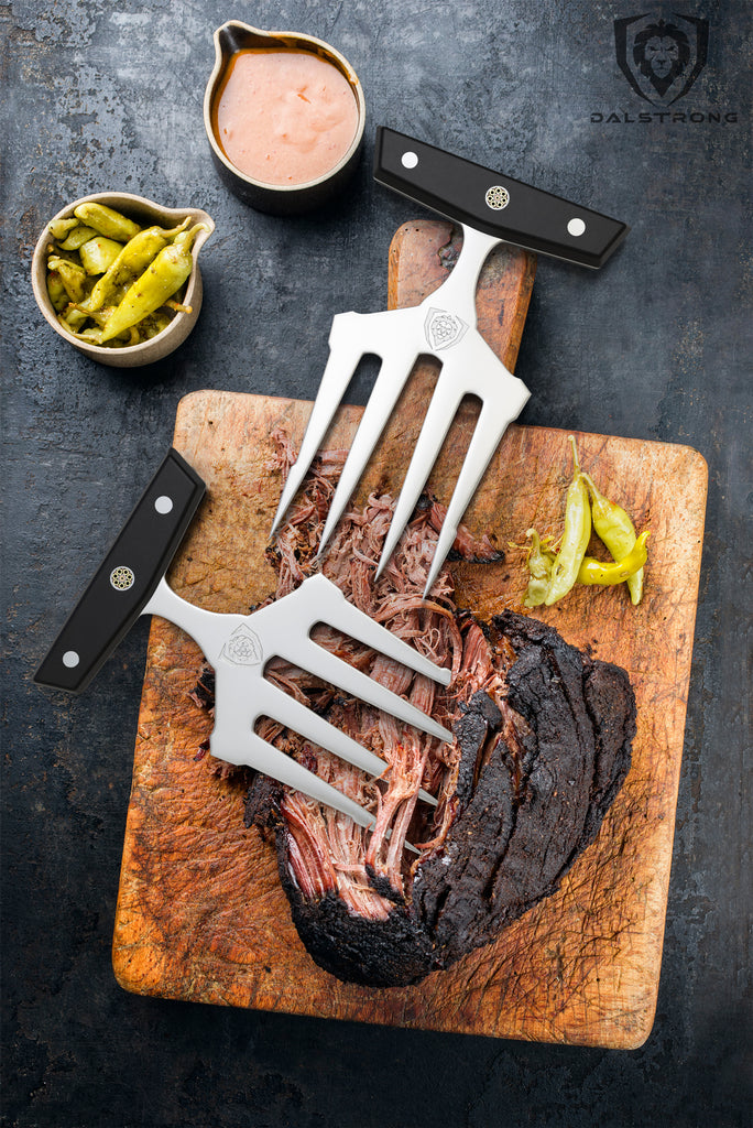 Cooked brisket on a wooden cutting board next to meat shredding claws