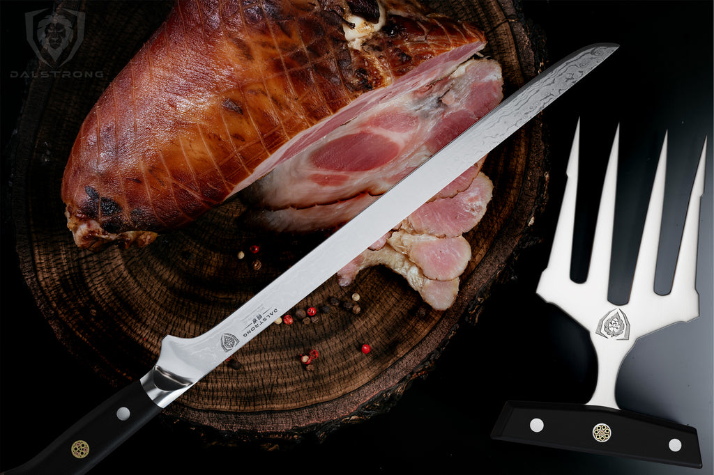 A large cooked ham next to a boning knife next to meat shredding claws