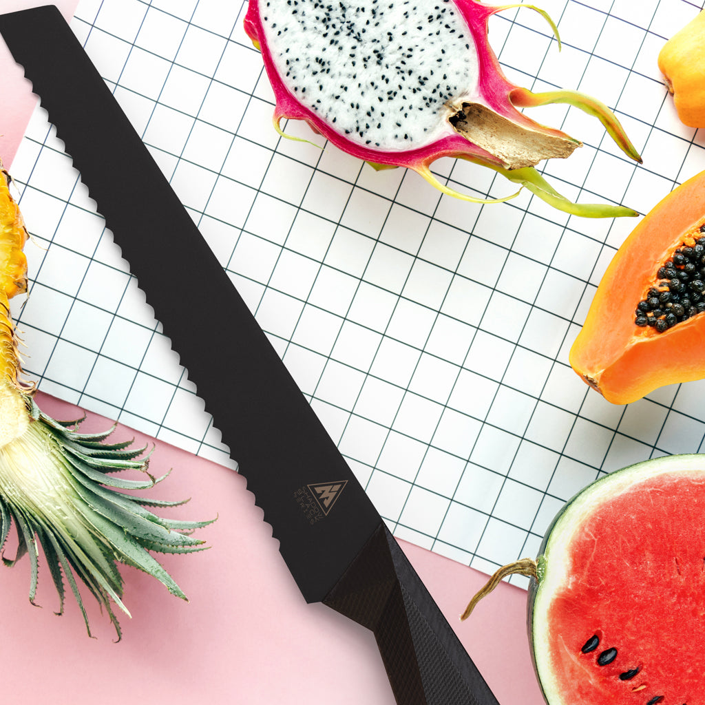 A black bread knife next to chopped fruit including dragon fruit