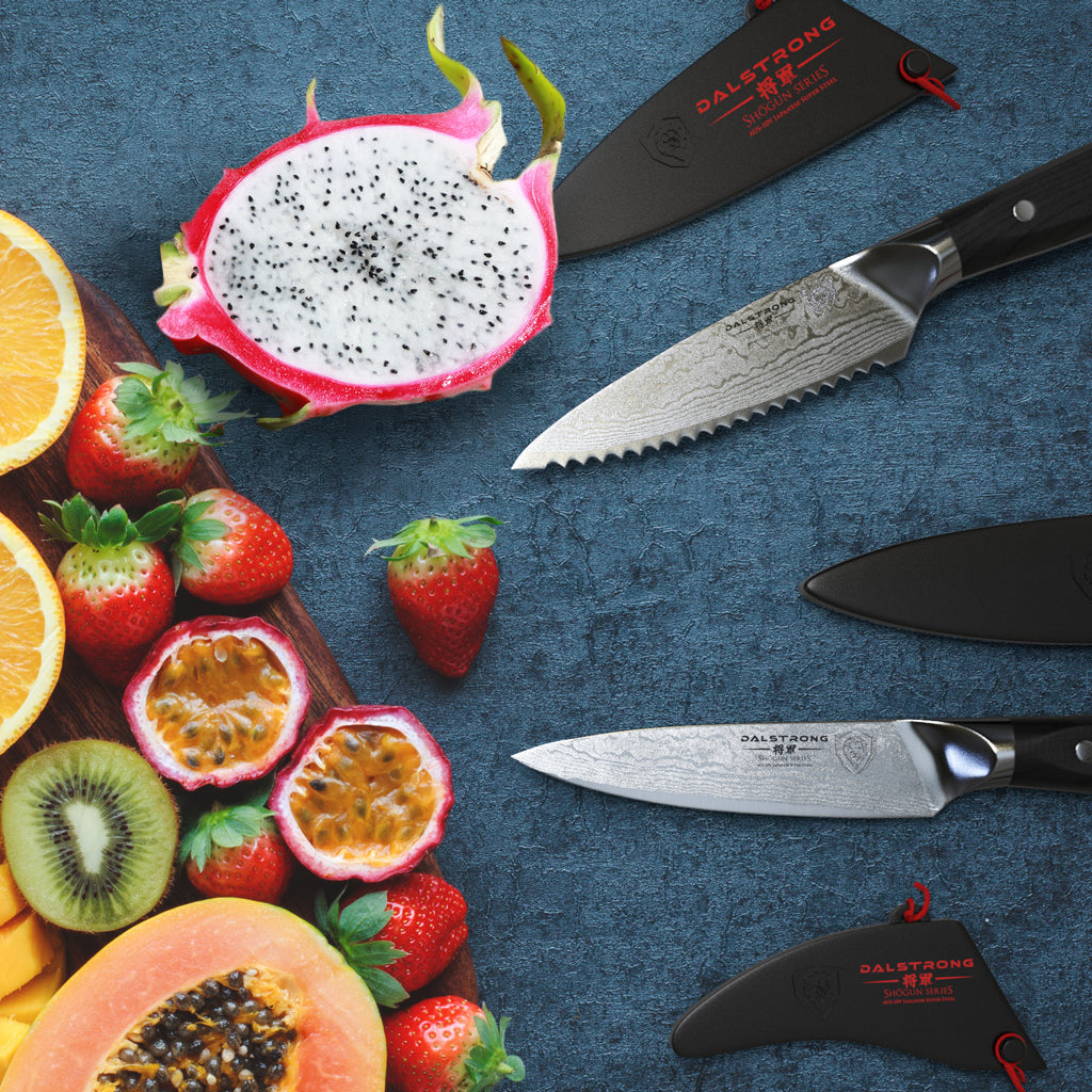 A pile of fruit next to two sharp paring knives against a blue background
