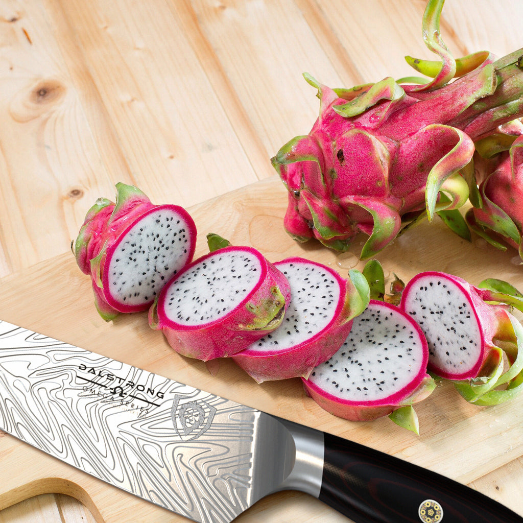 Close up on a chef knife next to chopped dragon fruit on a wooden background