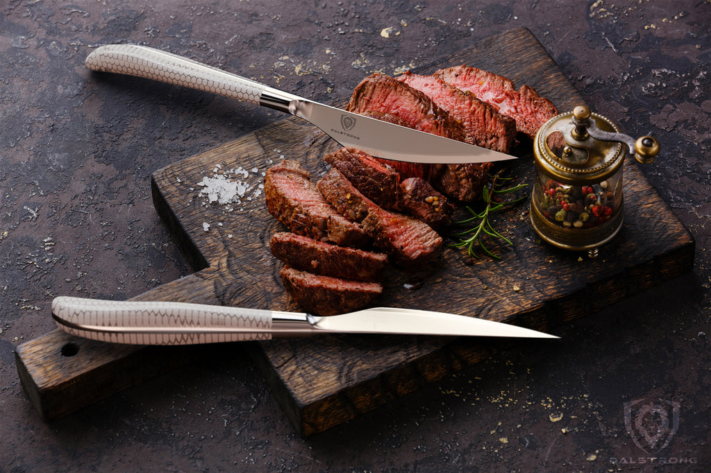 Two steak knives with white handles on a wooden cutting board next to chopped steak with a red center