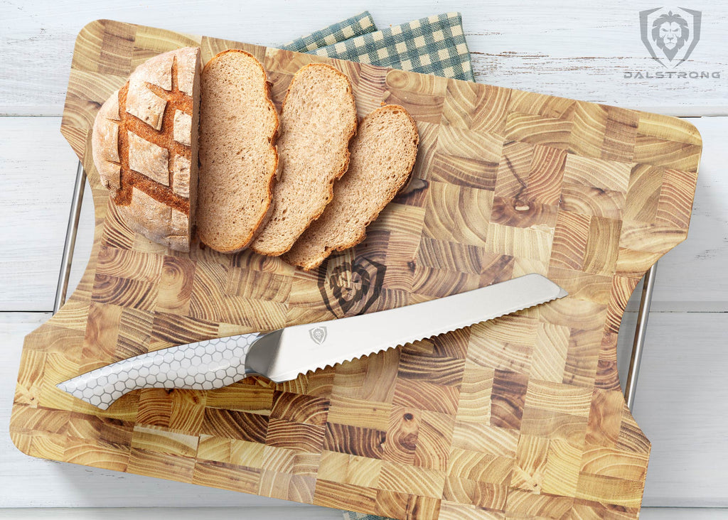 A serrated knife with a snake skin pattern handle on a large cutting board next to sliced bread
