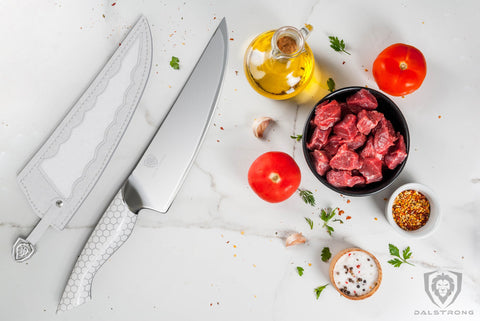 Chef knife with white handle on white marble next to small cups of sauces and diced meat