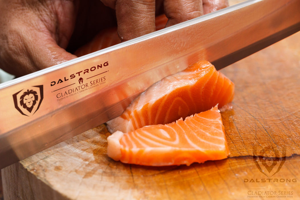Stainless Steel yanagiba knife slicing through raw fish on a wooden cutting board
