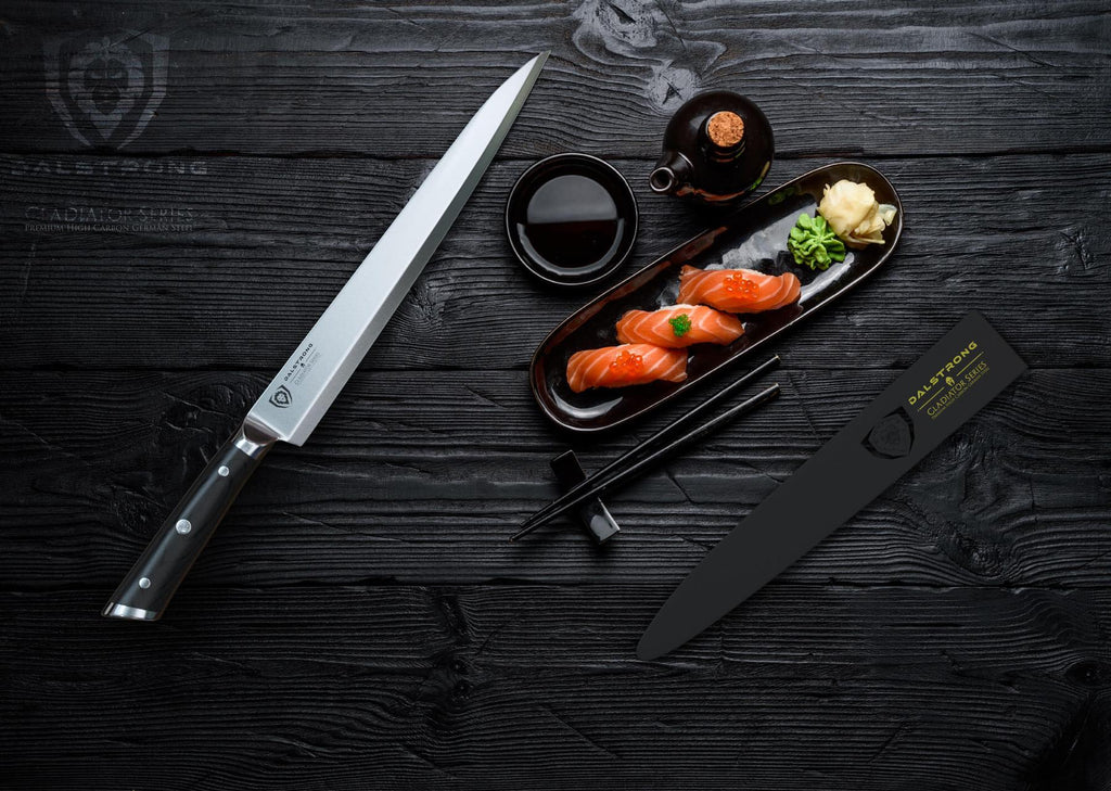 Yanagiba knife against a dark background next to sushi on a slim plate