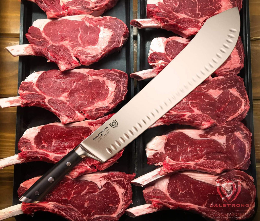 A large bullnose butcher knife resting on a bed of uncooked pieces of beef