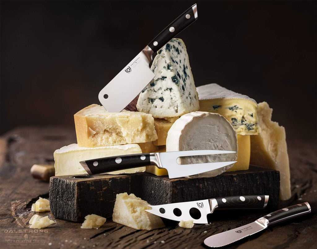 A pyramid of different cheese with a selection of cheese knives on top