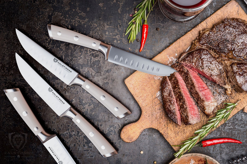 Four steak knives with white handles next to sliced cooked steak on a wooden cutting board