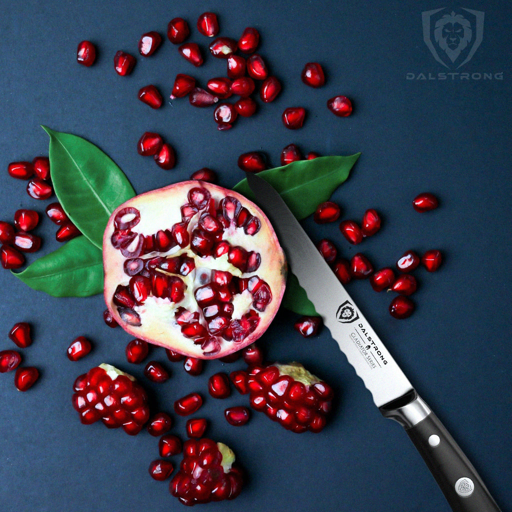A pomegranate half surrounded by red seeds on a dark blue surface