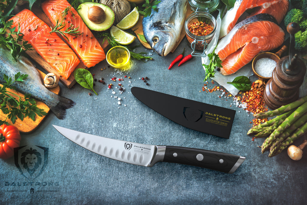 Fillet knife and sheath surrounded by uncooked fish and vegetables on a blue surface