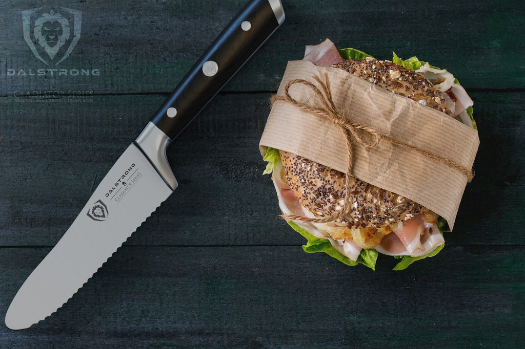 Serrated utility knife on a dark wooden surface next to a wrapped sandwich