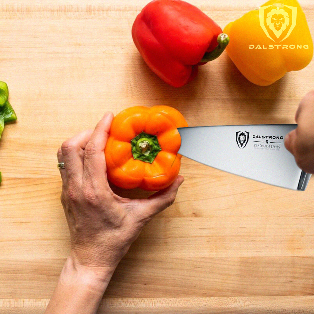A kitchen knife cutting into the top of an orange pepper next to other colored peppers