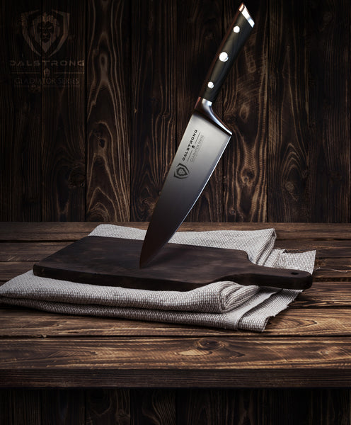 Dalstrong Gladiator Series Chef Knife balancing on a dark brown wooden cutting board by the tip