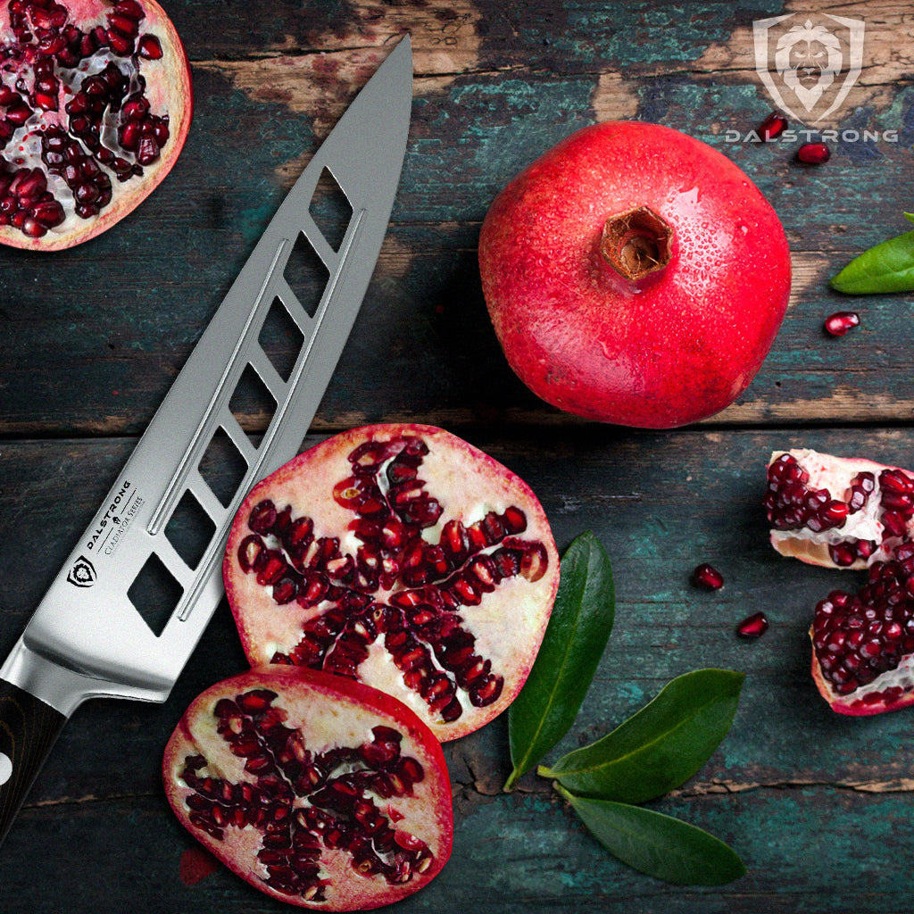 Vegetable slicing knife with hollow grooves next to a sliced pomegranate