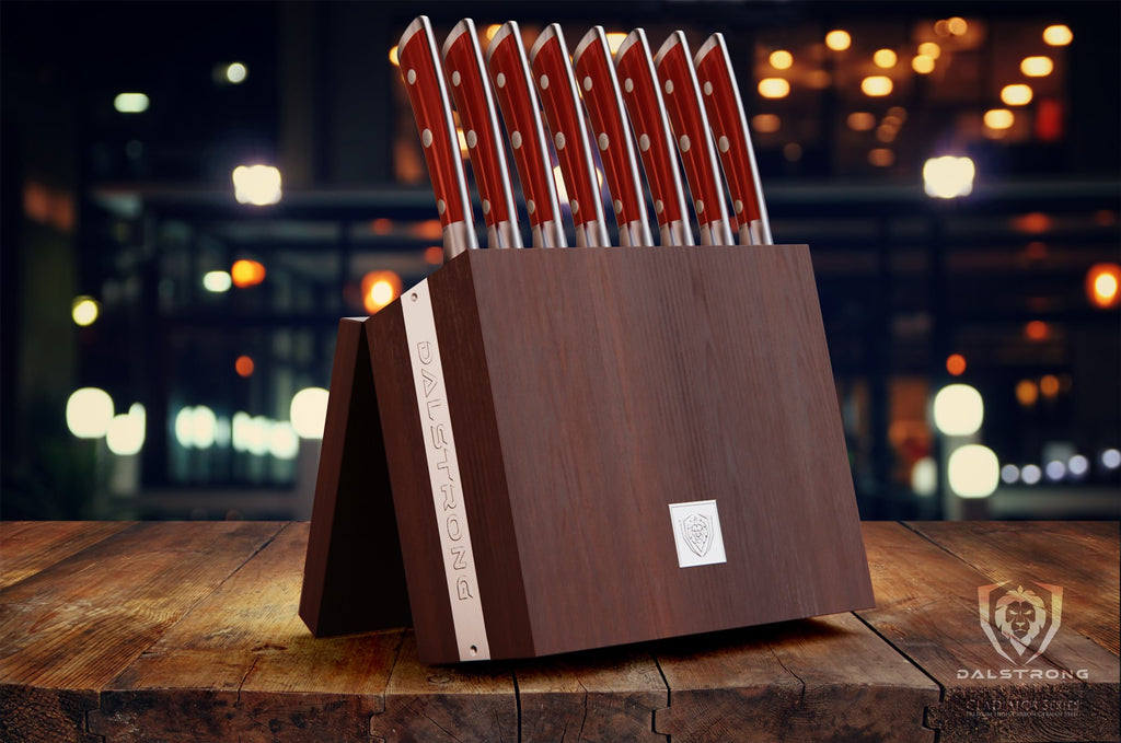 Wooden knife block set with eight red handled knives with lights in the background