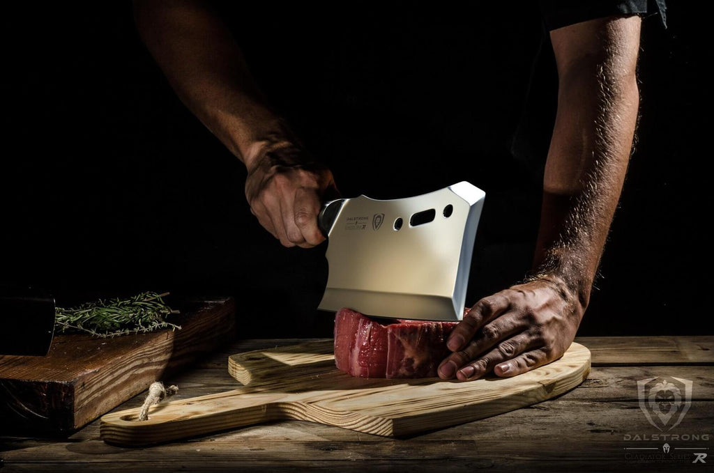 Man uses large cleaver to chop raw piece of red meat
