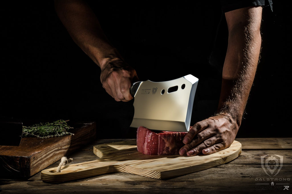 Man cutting uncooked meat on a wooden cutting board with a large cleaver knife