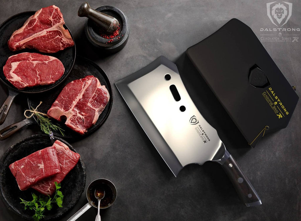 Four uncooked pieces of red meat next to a large cleaver against a dark surface