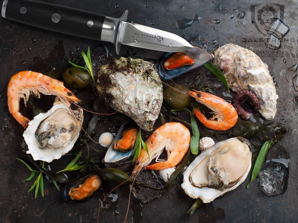 Prawns and oysters and clams next to a oyster shucking knife on a black surface