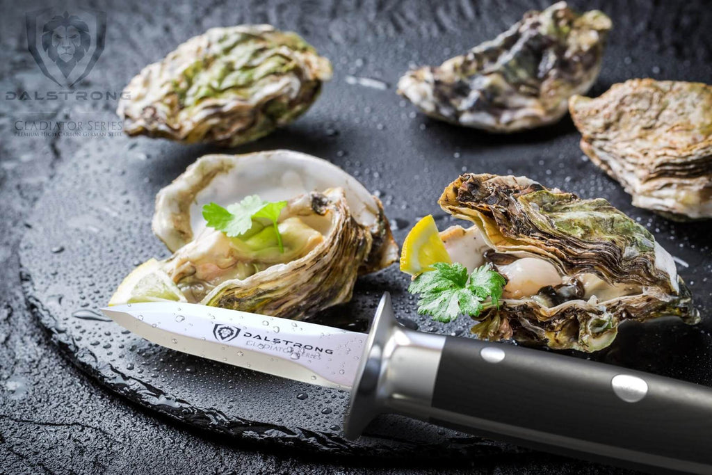 An oyster shucking knife next to a dark plate of oysters