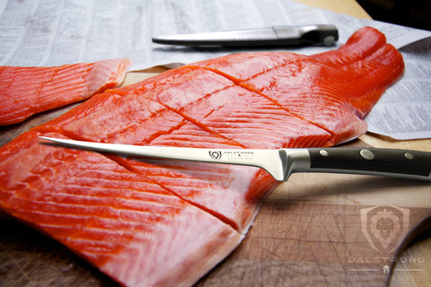 Dalstrong Gladiator Series Fillet Knife resting on a sliced fish that is atop a kitchen counter