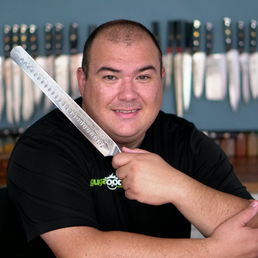 Chef Guga poses in a black tshirt holding a dalstrong carving and slicing knife