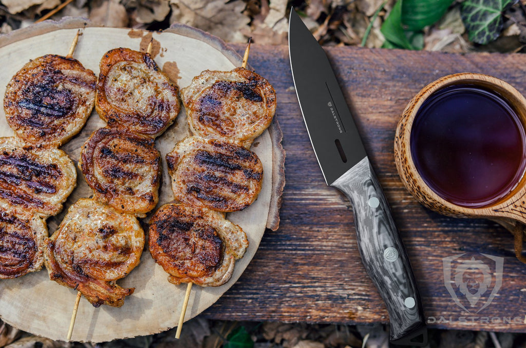 Three skewers of chicken outdoors next to a black paring knife