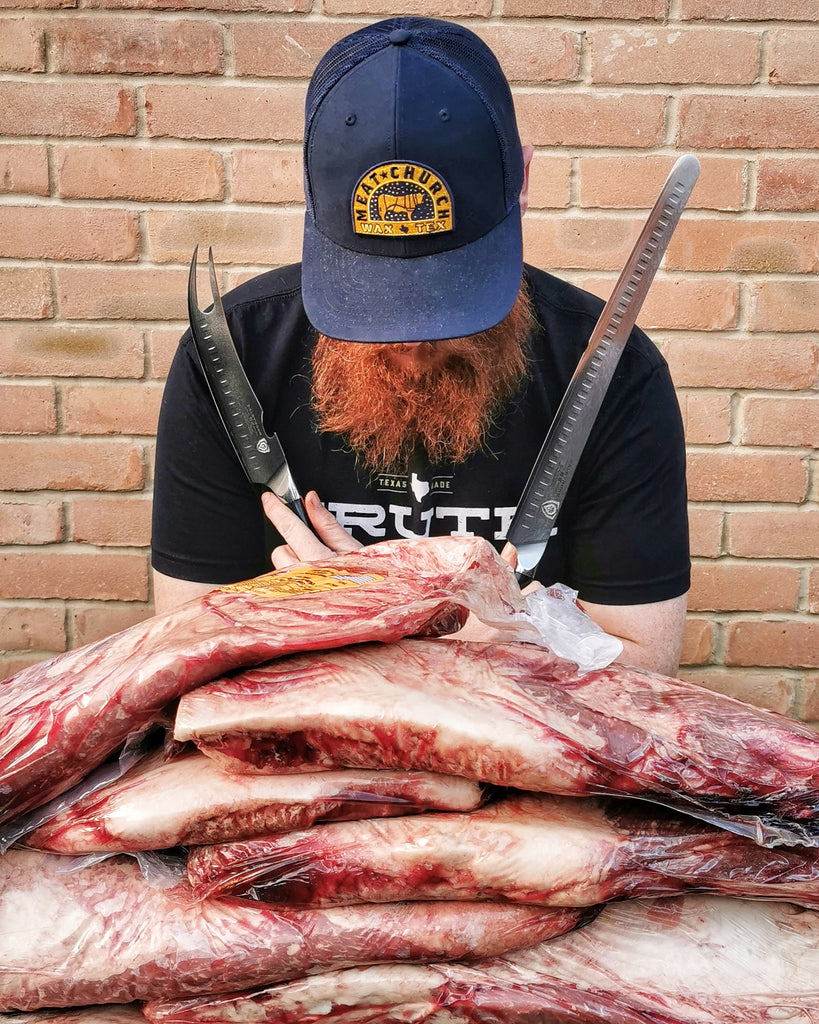 Artust BBQ (@ArtustBBQ) posing in front of meat holding two Dalstrong knives