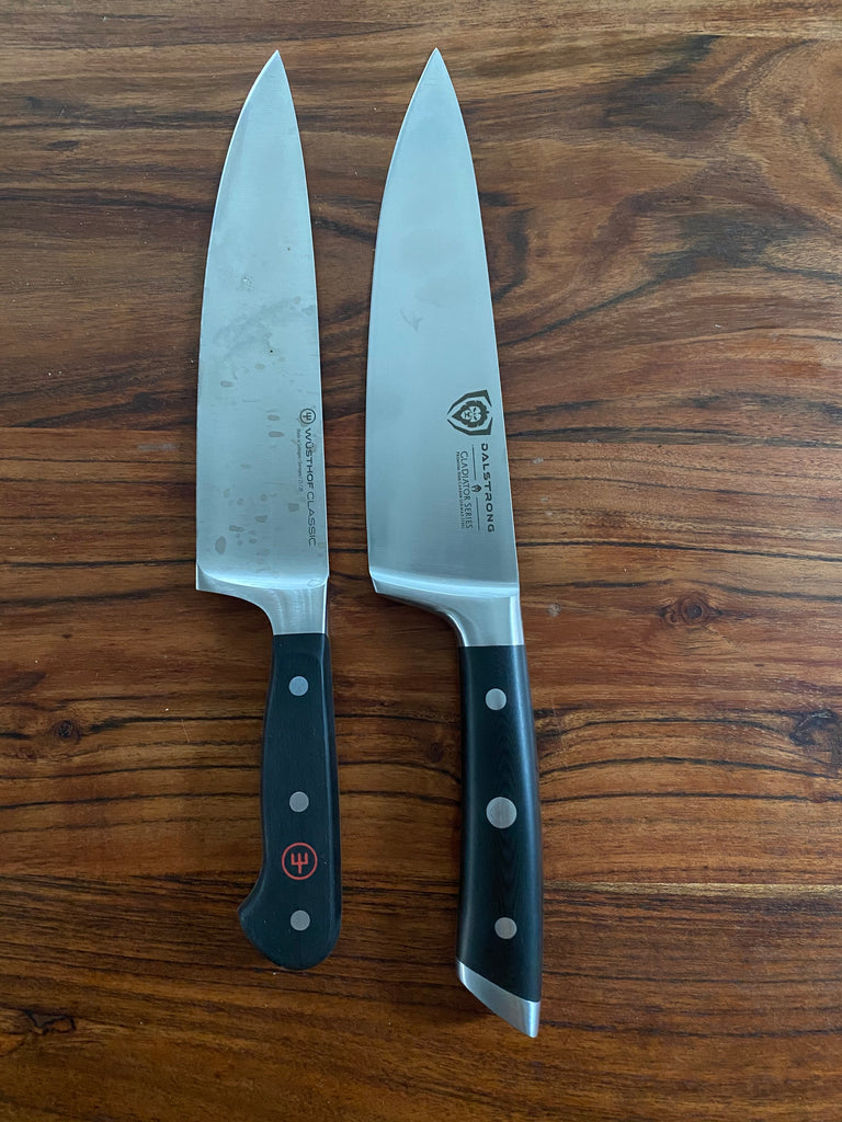 Wusthof knife next to a Dalstrong knife on a wooden surface