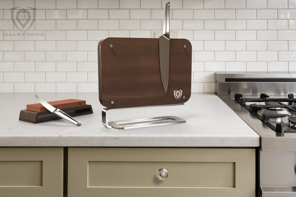 Brown Magnetic Knife Holder with one knife attached standing on granite kitchen counter next to a stove.