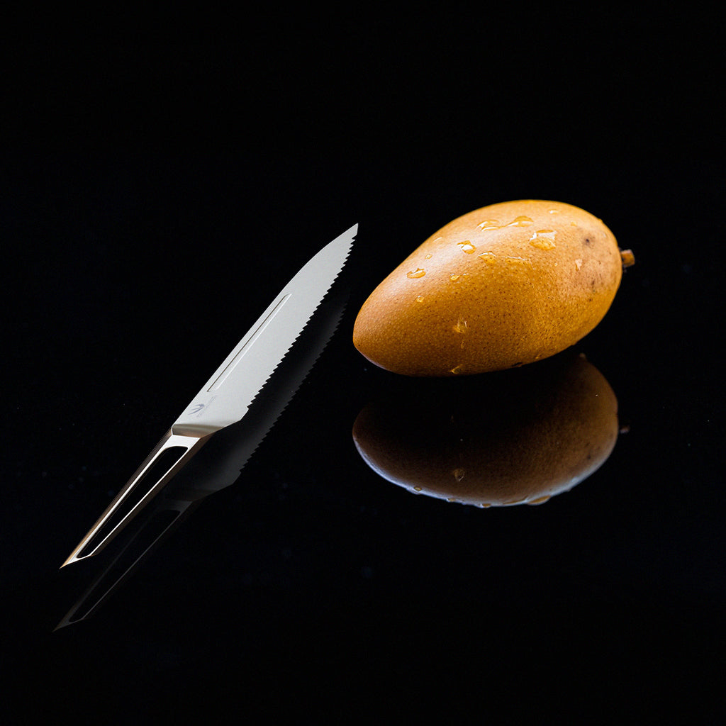 Stainless steel kitchen knife with hollow handle against a black surface beside a whole mango