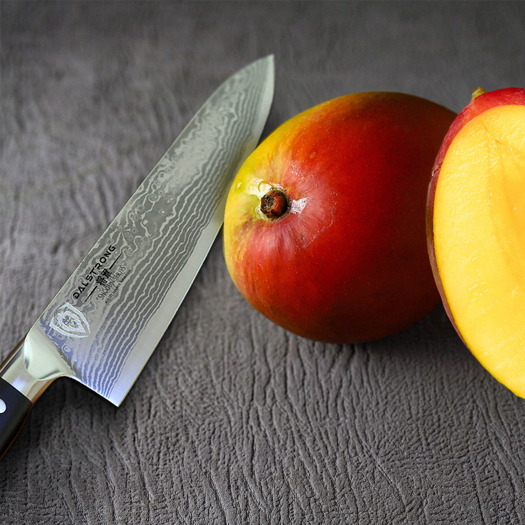 A razor sharp kitchen knife next to two pieces of mango on a wooden surface