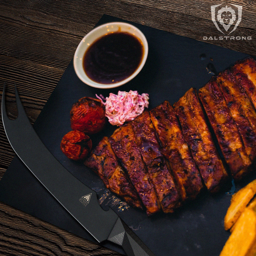 A black bbq knife with a pronged tip next to a rack of cooked ribs and bbq sauce