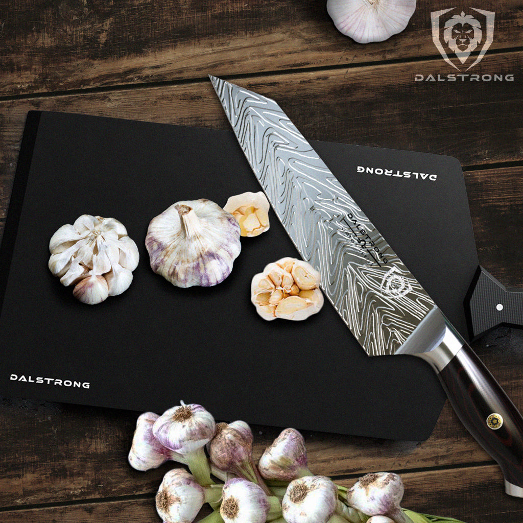 A sharp kitchen knife with a liquid blade pattern next to cloves of garlic on a black cutting board