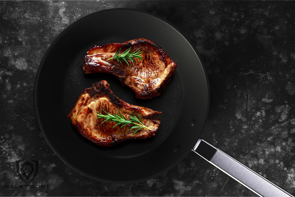 Two cooked pork chops in a black skillet with a silver handle