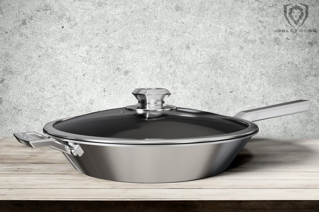 Stainless Steel Pan On A Light Brown Table with a grey wall for a background