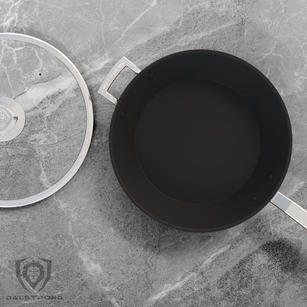 A black skillet with silver handles next to its own lid on a grey countertop
