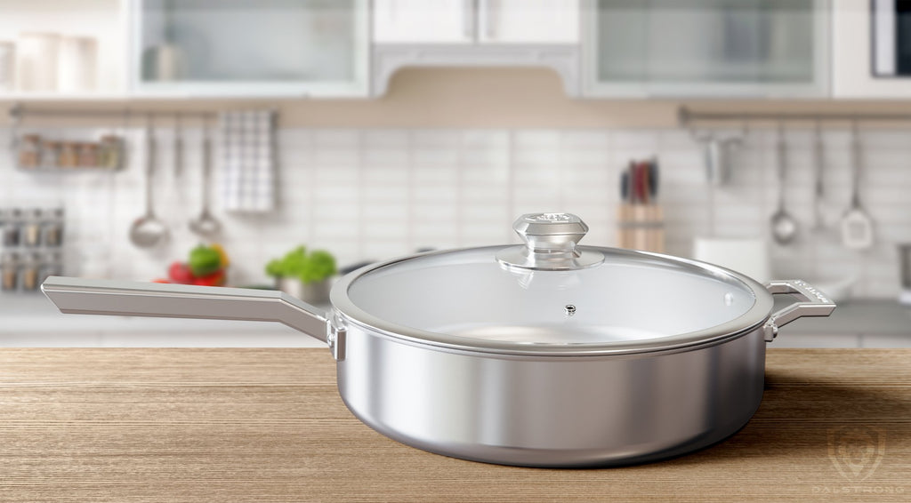 Oberon Series Saute Frying Pan on clean wooden kitchen counter with cooking utensils hanging on a wall in the distance