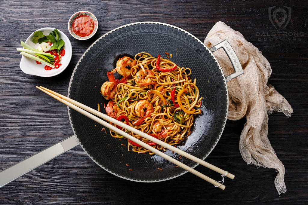 A black interior wok with cooked noodles and vegetables and chopsticks resting on its edge